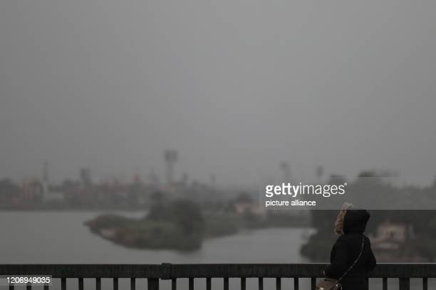 A woman in a rain coat looks out into the horizon as she stands on Abbas Bridge amid turbulent weather conditions At least 20people died in...