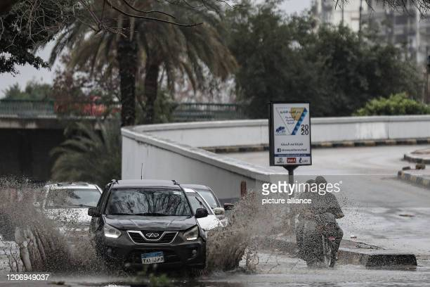 Cars splash into a puddle of water caused by heavy rain amid turbulent weather conditions At least 20people died in accidents linked to Egypt's...