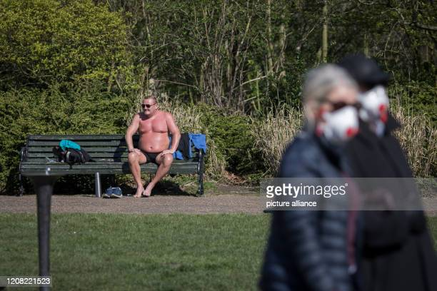 A man sunbathes as a couple wearing face masks walks past in Regents Park on the second day of a nationwide lockdown Photo Oliver Weiken/dpa