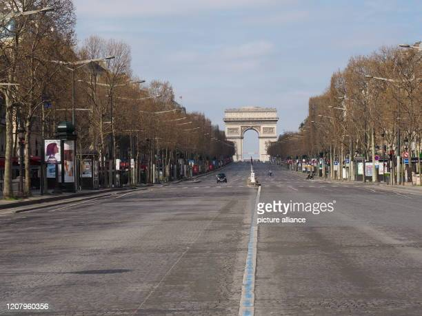 The Parisian boulevard ChampsElysees with the triumphal arch is almost deserted In Frence there is a curfew because of the Corona crisis People are...