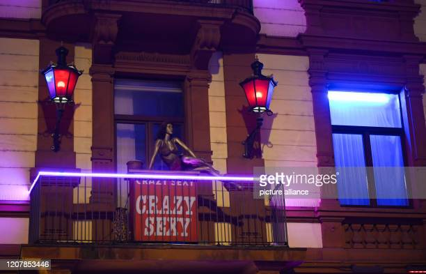 A mannequin and red lanterns can be seen on a balcony of the brothel Crazy Sexy in the evening on Elbestraße in Frankfurt's station district The red...