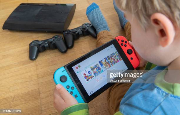 March 2020, Lower Saxony, Hanover: ILLUSTRATION - A child is playing with a Nintendo Switch game console while a Sony Playstation 3 with two...