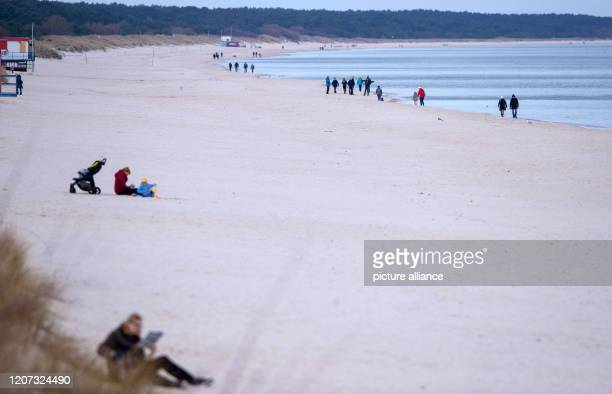 March 2020, Mecklenburg-Western Pomerania, Zinnowitz: Only a few vacationers are on the beach at the pier. The access roads to Baltic Sea islands...