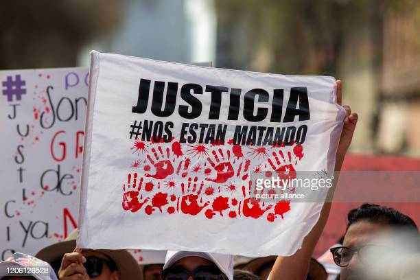 A woman holds a flag with the inscription Justice on International Women's Day After several sensational murders of women tens of thousands of...