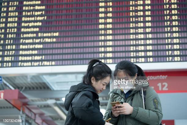 Junnan Ma and Mingshuo Xiao students from China at TU Dresden are standing in front of a departure board at Dresden Airport Numerous flights are...