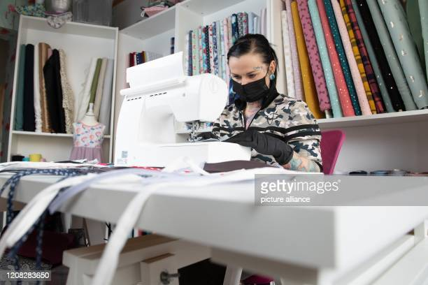 March 2020, Saxony, Zwickau: Daniela Beck, tattoo artist, sews mouthguards with a mouthguard on a sewing machine. Beck and other women from Zwickau...