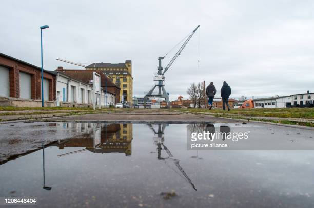 A disused crane stands in the science harbour and is reflected in a puddle of rain It continues to change in the region around the state capital...