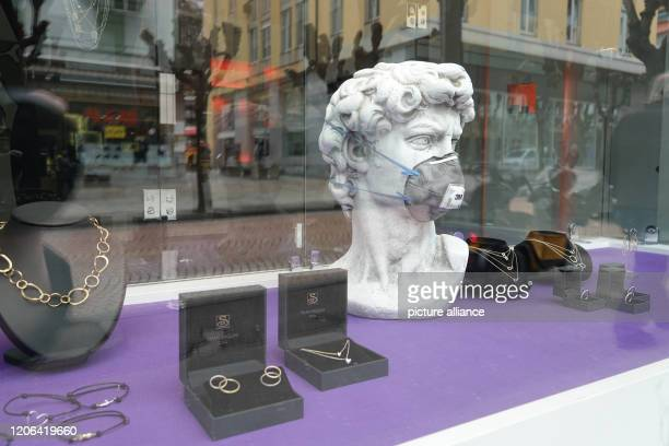 In a shop window of a jewellery shop there is a replica of the head of Michelangelo's sculpture David with a mouthguard Bellinzona the capital of the...