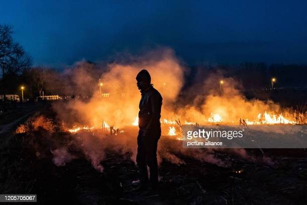 March 2020, Turkey, Edirne: A migrant stands next to a fire in the Turkish-Greek border province of Edirne. Photo: Yasin Akgul/dpa