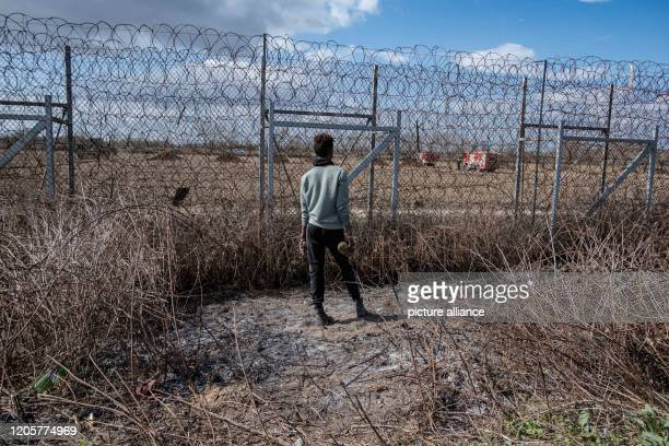 March 2020, Turkey, Pazarkule: A migrant stands at the border fence on the Turkish-Greek border. During clashes with Greek security forces, tear gas...