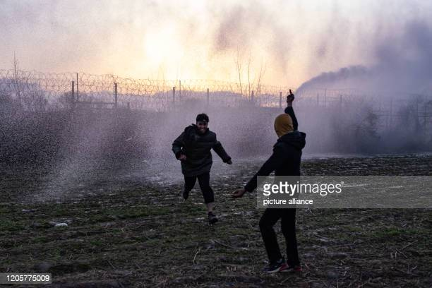 March 2020, Turkey, Pazarkule: Migrants are in a confrontation with Greek security forces at the Turkish-Greek border. Tear gas and water cannons...