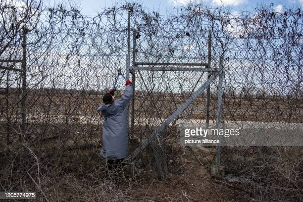 March 2020, Turkey, Pazarkule: Migrants stand at the border fence on the Turkish-Greek border and try to cut through the fence with wire scissors....