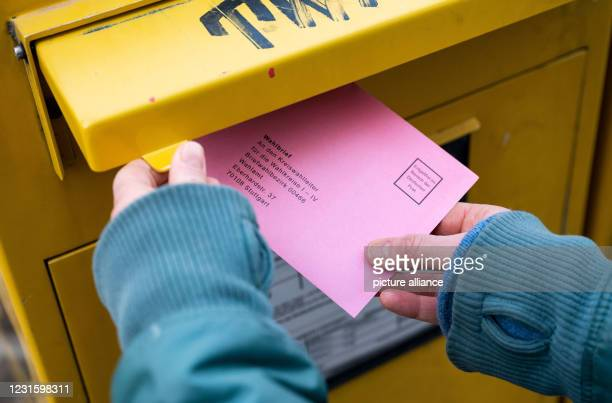 March 2021, Baden-Wuerttemberg, Stuttgart: A woman throws an election letter for the state election in Baden-Württemberg into a mailbox. Photo:...