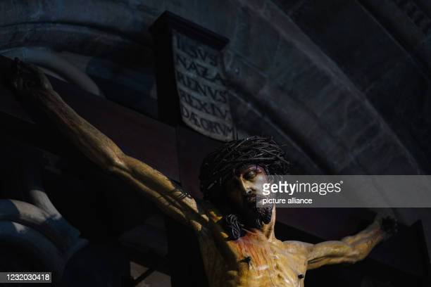 March 2021, Bavaria, Bamberg: Light falls on a figure of the crucified Jesus Christ in the cathedral. The churches are preparing for Easter in the...