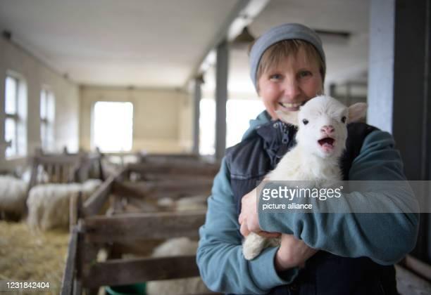 March 2021, Brandenburg, Roskow: Farmer Katja Behling from the Skuddenhof in the Roskow district of Weseram holds a still nameless ram born on in her...