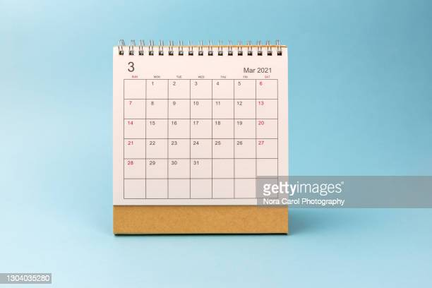 march 2021 desk calendar on blue background - thursday stock pictures, royalty-free photos & images
