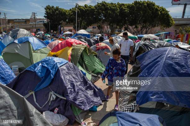 """March 2021, Mexico, Tijuana: A child walks through tents at a migrant camp on the grounds of the National Institute for Migration near the """"El..."""