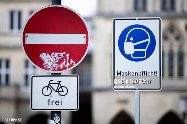 """March 2021, North Rhine-Westphalia, Münster: A sign stating that masks are mandatory stands next to a """"no passing"""" sign. Photo: Rolf Vennenbernd/dpa"""