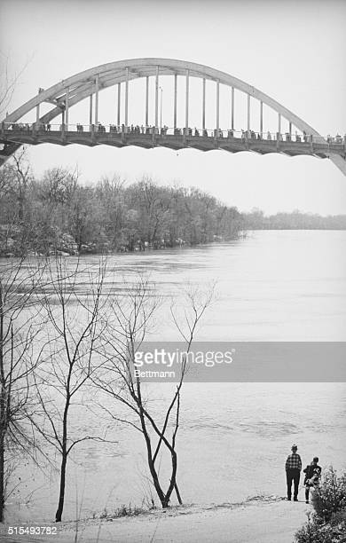 March 21, 1965 - Selma, Alabama: Lone Selma resident stands on bank of Alabama river and watches long line of racial demonstrators silhouetted...