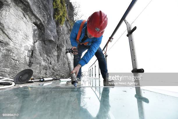 ZHANGJIAJIE March 21 2018 A worker seals the joint of glass plates on the glass pavement at Tianmenshan scenic area in Zhangjiajie central China's...