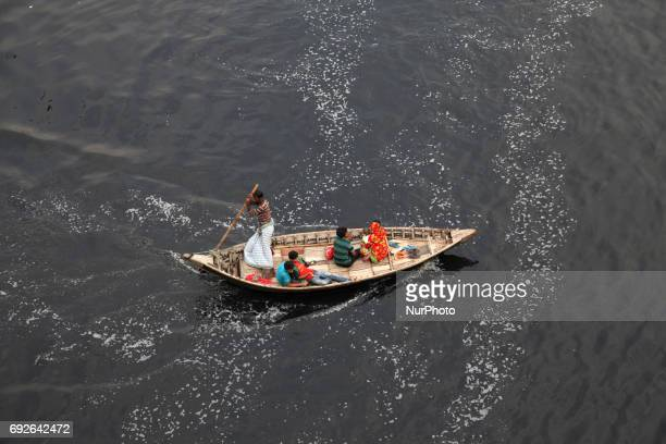March 22 2017 Dhaka Bangladesh A Bangladeshi boatman ride his boat and crossing in the polluted water near the riverbank of Buriganga on the eve of...