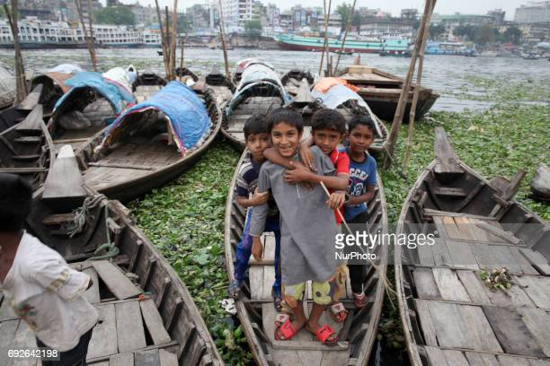 March 22 2017 Dhaka Bangladesh A group of childrens stand on the boat to takes photos near the riverbank of Buriganga on the eve of World Environment...