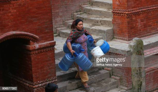 A woman arrives with empty jars to fill water from the traditional stone tap in Kathmandu Nepal March 22 the World Water Day