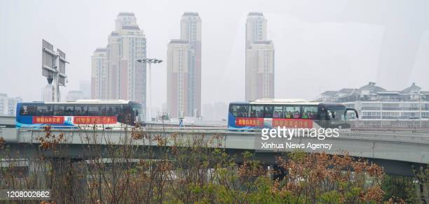 March 22, 2020 -- Buses carrying medical workers head for the airport in Wuhan City, central China's Hubei Province, March 22, 2020. On Sunday, 145...
