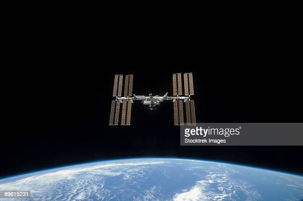 march 25, 2009 - the international space station, backdropped by the blackness of space and earth's horizon. - space station stock photos and pictures