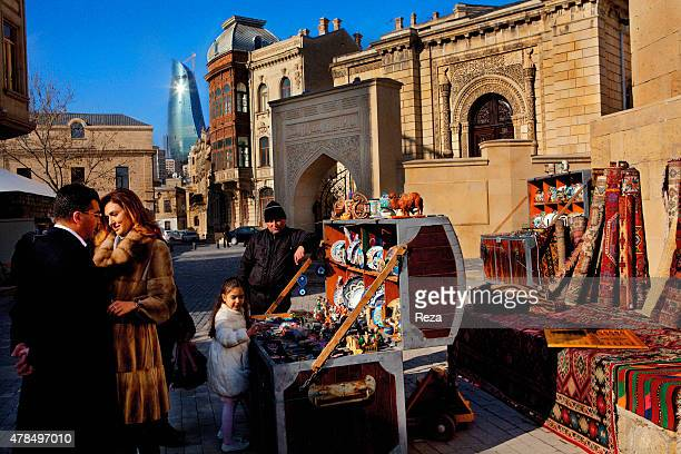 March 26 Old City, Baku, Azerbaijan. An Azerbaijani couple is posing for a video-clip in the Old City of Baku with their daughter. They stop at an...