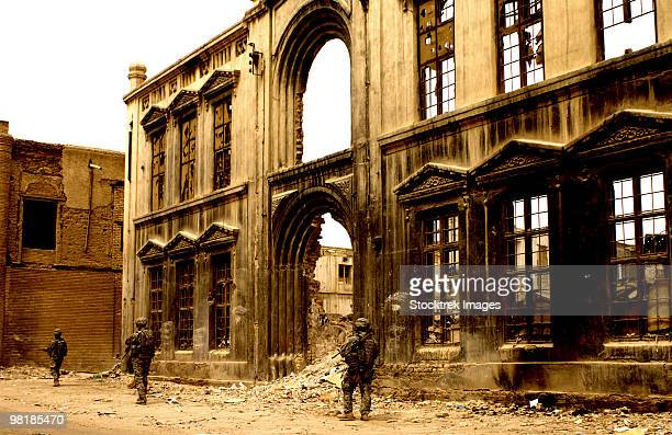 March 27, 2008 - Soldiers patrol past the facade of a demolished building in Baghdad, Iraq.