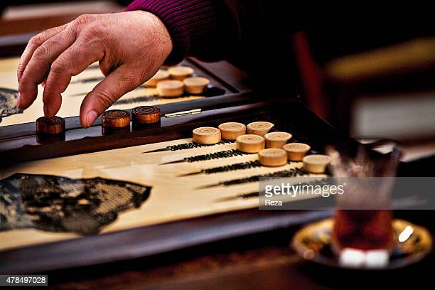 March 27 Old City, Baku, Azerbaijan. Men play backgammon in the Old City while drinking tea. Backgammon has ancient roots in the Persian Empire and...