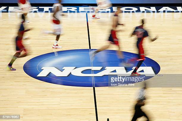 Players dribble the ball on the NCAA logo at half court during the NCAA Division 1 Men's Basketball Championship Elite Eight round game between the...