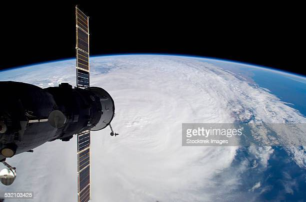 march 30, 2006 - cyclone glenda and a docked soyuz spacecraft. - space station stock photos and pictures