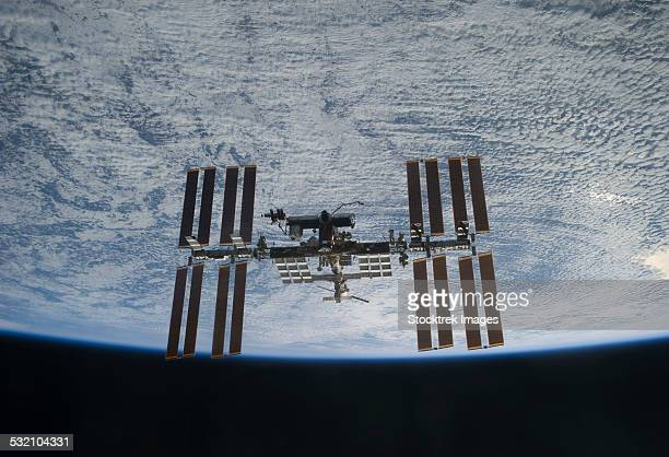 March 7, 2011 - The International Space Station backdropped against clouds over Earth.
