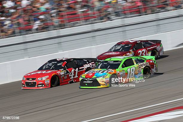 Regan Smith StewartHass Racing Chevrolet Impala SS and David Ragan Joe Gibbs Racing Toyota Camry race out of turn four during the NASCAR Sprint Cup...