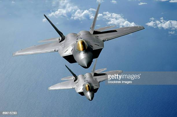 March 9, 2009 - Two F-22 Raptors fly over the Pacific Ocean during a theater security mission as part of a deployment to Andersen Air Force Base, Guam.