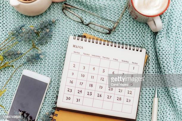 march calendar  in feminine workspace with lavender flowers, coffee , eyeglasses and pen - monthly event stock pictures, royalty-free photos & images