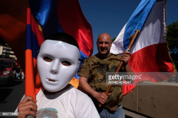 A march participant wears a white mask as others hold Armenian flags during a march in commemoration of the 103rd anniversary of the mass killings of...
