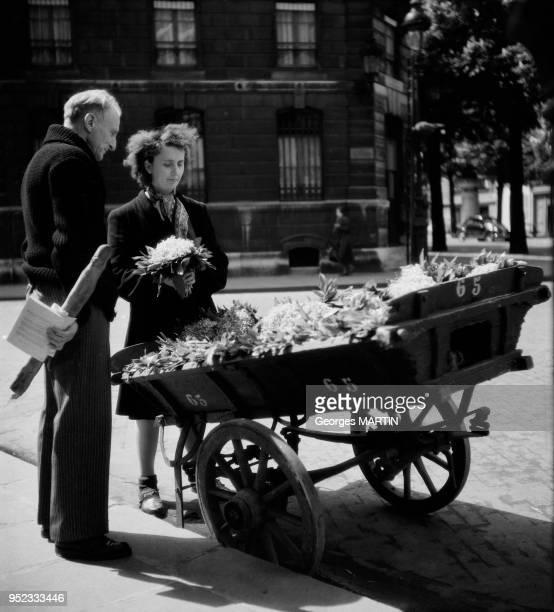 Marchande de muguet pour la fete du 1er mai, circa 1960 a Paris, France.