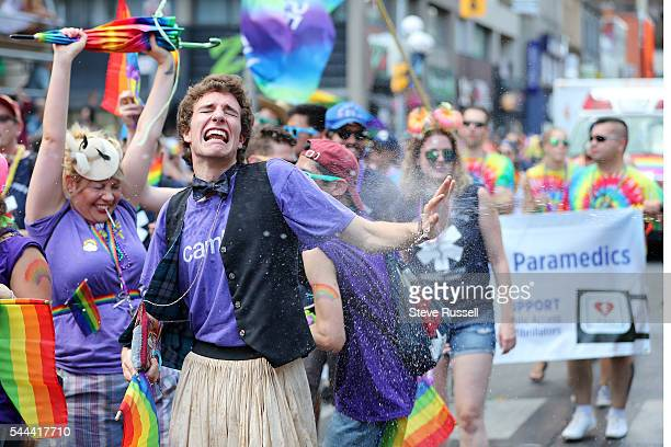 Marcher gets sprayed during the the 2016 Toronto Pride parade along Yonge Street in Toronto July 3 2016