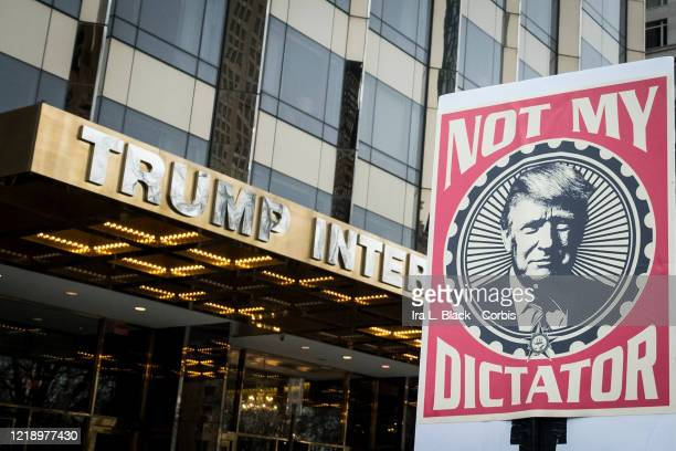 A marcher holds a sign that says Not My Dictator with a picture of Donald Trump in front of Trump International Tower during the Woman's March in the...