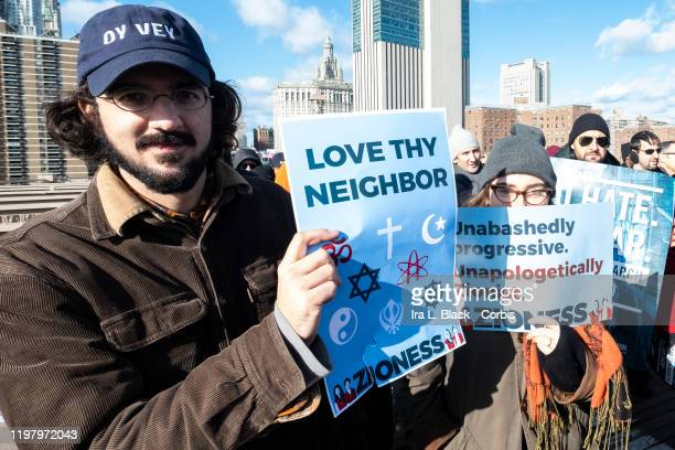 """Marcher walking across the Brooklyn Bridge wearing a hat that says """"Oy Vey"""" and carry a sign that says """"Love Thy Neighbor"""" with symbols of various..."""