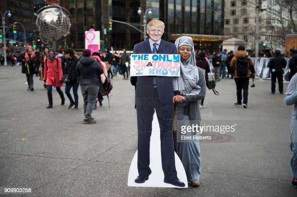 A marcher with standee of Donald Trump and a placard referring to alleged remarks by the US President at the 2018 Women's March in New York City on...