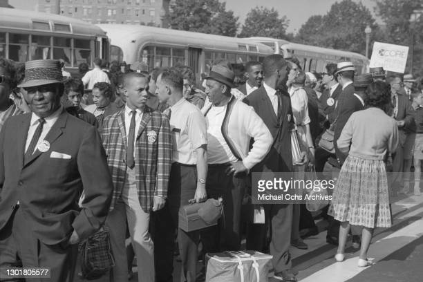 """Marchers arrive by bus holding a """"CORE Downtown"""" sign before the March on Washington on August 28, 1963 in Washington DC."""
