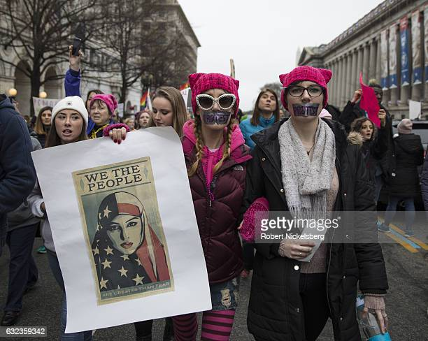 Marchers attending the Women's March on Washington hold up women's rights signs critical of President Donald Trump on January 21 2017 in Washington...