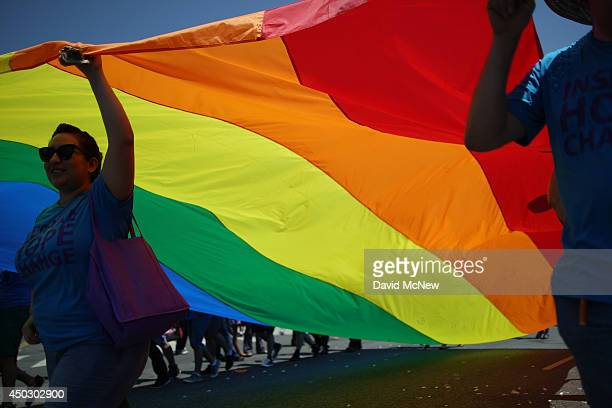 Marchers carry a rainbow flag in the LA Pride Parade on June 8 2014 in West Hollywood California The LA Pride Parade and weekend events this year are...