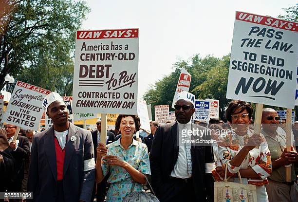 Marchers carry antisegregation signs furnished by the United Auto Workers at the March to Washington More than 200000 people participated in the...