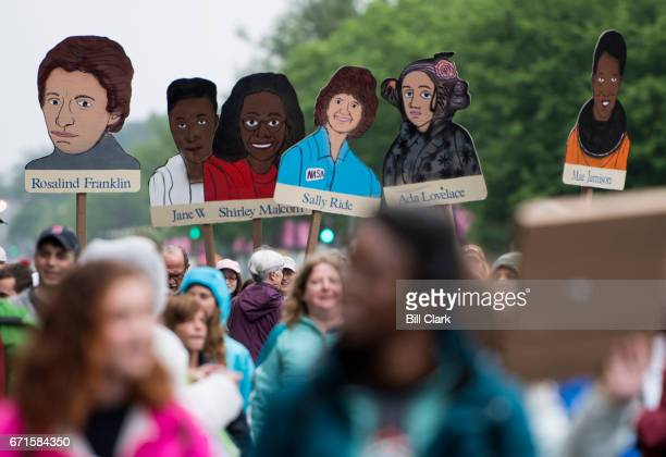 Marchers carry portraits of women scientists down Constitution Avenue in Washington during the Science March on Earth Day Saturday April 22 2017...