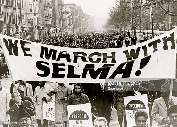 Marchers carrying banner lead way as 15000 parade in Harlem We march with Selma